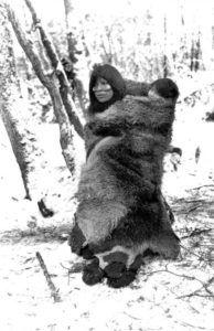 Mujer Selknam con su hijo abrigado con piel de guanaco