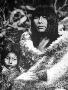 Mujer Selknam con su hijo, con pintura facial.