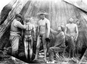 Jóvenes Selknam pintándose el cuerpo.